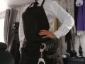 Whte shirt and black cotton tie with black PVC skirt under a black cotton full length hairdressing  apron