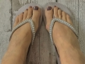 Bare feet in silver flip flops