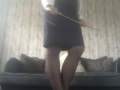 A white blouse, navy blue satin skirt, black seamed stockings and black suedette, cuban heel, ankle strap shoeholding a hooked ratan cane